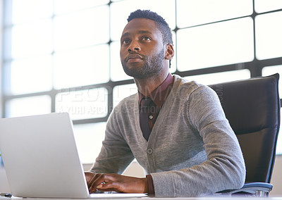 Buy stock photo Shot of a thoughtful young businessman using a laptop in an office