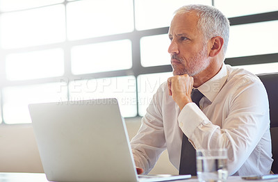 Buy stock photo Shot of a mature businessman using a laptop in an office