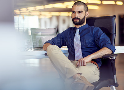 Buy stock photo Shot of a young businessman sitting at his desk in an office