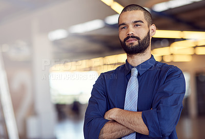 Buy stock photo Shot of an ambitious young businessman standing with his arms folded in an office