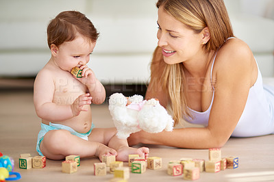 Buy stock photo Shot of an adorable baby girl and her mother playing with wooden blocks at home