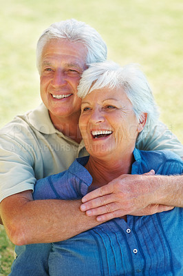 Buy stock photo Closeup of senior couple smiling and looking away while sitting on grass with man embracing woman from behind