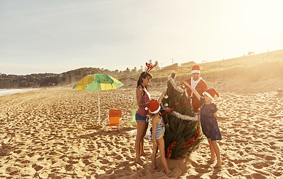 Buy stock photo Shot of a young family spending Christmas at the beach