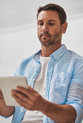 Buy stock photo Cropped shot of a businessman using his digital tablet at home