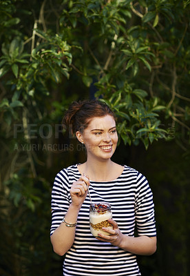 Buy stock photo Shot of a young woman eating a granola and yogurt parfait outdoors
