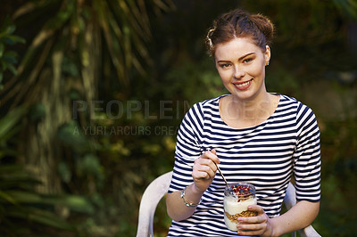 Buy stock photo Portrait of a young woman eating a granola and yogurt parfait outdoors