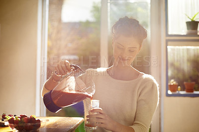 Buy stock photo Shot of a young woman making a fruit smoothie at home