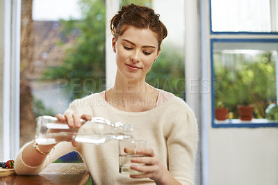 Buy stock photo Shot of a young woman pouring a glass of water at home