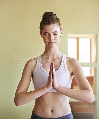 Buy stock photo Shot of a woman with her hands in prayer position while doing yoga