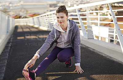 Buy stock photo Full length shot of an attractive young woman stretching before her morning run