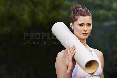 Buy stock photo Cropped shot of a young woman holding her yoga mat while standing outside