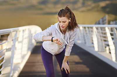 Buy stock photo Cropped shot of an attractive young woman checking her watch an early morning jog
