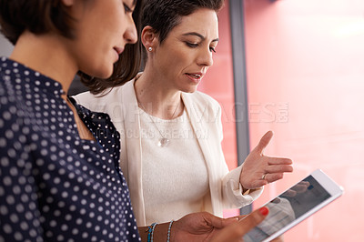 Buy stock photo Cropped shot of two businesswomen talking in the hallway