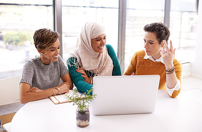 Buy stock photo Shot of a team of colleagues having a meeting around a laptop in a modern office