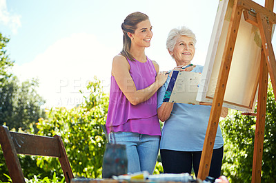 Buy stock photo Shot of a senior woman and her adult daughter painting in a park