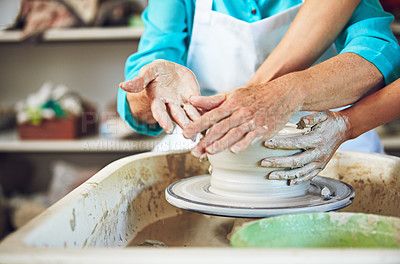 Buy stock photo Cropped shot of a senior couple making a ceramic pot together in a workshop