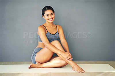 Buy stock photo Shot of a sporty young woman sitting against a grey background