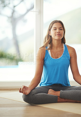Buy stock photo Cropped shot of a young woman practicing the art of meditation at home