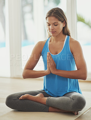Buy stock photo Full length shot of a young woman practicing the art of meditation at home