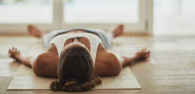 Buy stock photo Shot of a young woman lying on her yoga mat after a workout