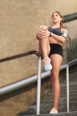 Buy stock photo Full length shot of an attractive young athlete warming up before an outdoor workout