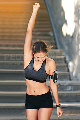 Buy stock photo Cropped shot of an attractive young athlete standing with her arm raised after an outdoor workout