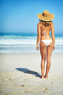 Buy stock photo Rearview shot of a gorgeous young woman in a bikini at the beach