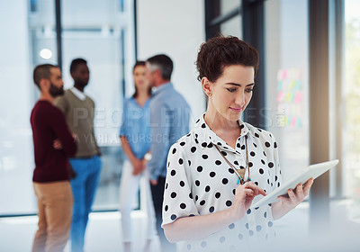 Buy stock photo Cropped shot of a businesswoman working in the office with her colleagues in the background