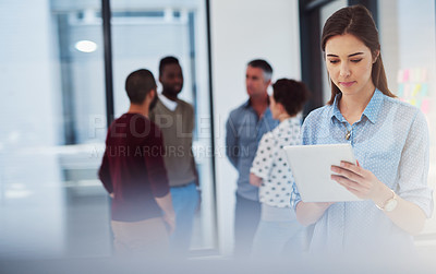 Buy stock photo Cropped shot of a young businesswoman working in the office with her colleagues in the background