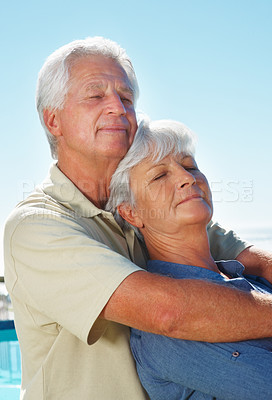 Buy stock photo Senior couple standing together and enjoying the peaceful weather with man embracing woman from behind