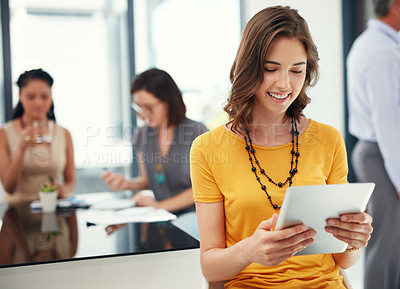Buy stock photo Cropped shot of a young businesswoman using her digital tablet during a meeting