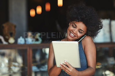 Buy stock photo Shot of a young woman using a digital tablet while talking on the phone at a cafe