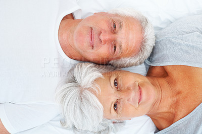 Buy stock photo Closeup portrait of senior couple lying together on bed and smiling