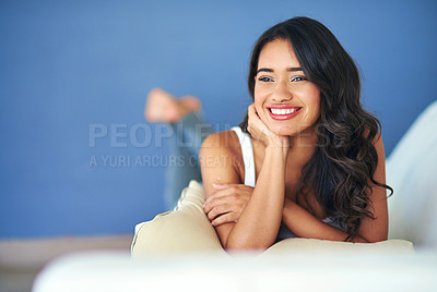 Buy stock photo Shot of a young woman looking thoughtful while lying on her living room sofa