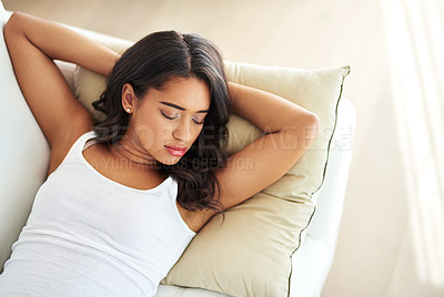 Buy stock photo Shot of a young woman asleep on her sofa
