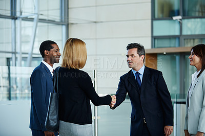 Buy stock photo Shot of businesspeople shaking hands in the lobby of an office building