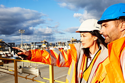 Buy stock photo Shot of a two workers standing on a large commercial dock