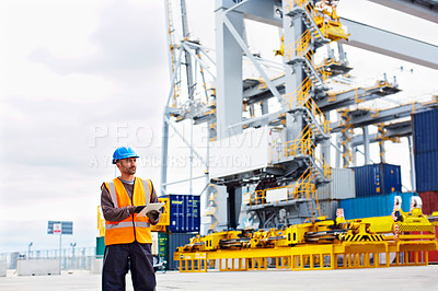 Buy stock photo Shot of a young man in workwear using a digital tablet while standing on a large commercial dock