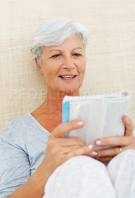 Buy stock photo Senior woman sitting on bed and reading a book