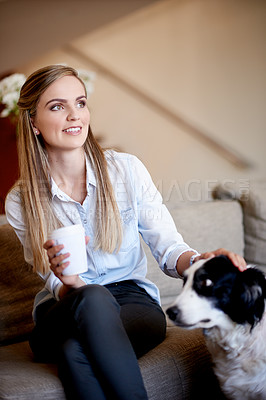 Buy stock photo Shot of an attractive young woman spending time with her dog at home