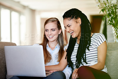 Buy stock photo Shot of two young friends using a laptop together at home