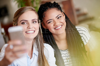 Buy stock photo Shot of two young friends taking a selfie