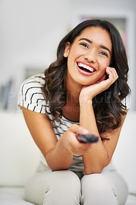 Buy stock photo Cropped shot of a young woman watching TV while relaxing on her sofa at home