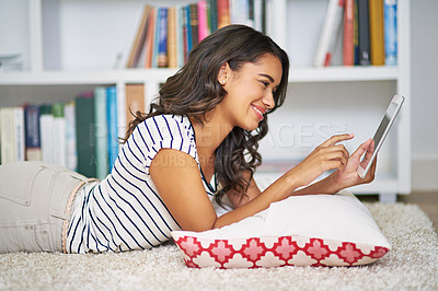 Buy stock photo Cropped shot of a young woman using her tablet while relaxing at home