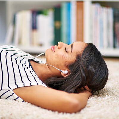 Buy stock photo Cropped shot of a young woman listening to music while relaxing at home