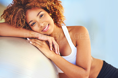 Buy stock photo Shot of a young woman leaning against her exercise ball