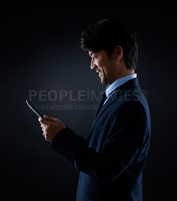 Buy stock photo Studio shot of a businessman using a digital tablet against a dark background