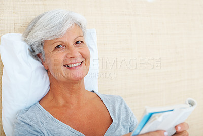 Buy stock photo Closeup portrait of smiling senior woman reading a book while relaxing on bed