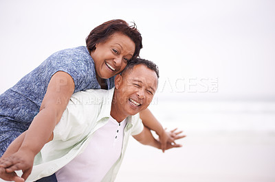 Buy stock photo Shot of a mature man giving his wife a piggyback ride at the beach