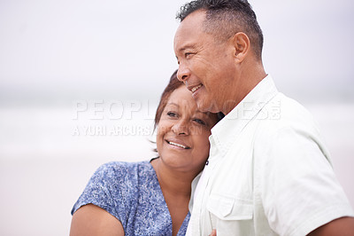 Buy stock photo Shot of a loving mature couple enjoying themselves at the beach